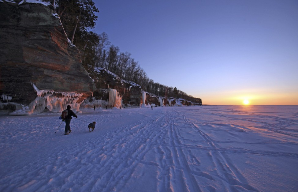 Woman walks dog on frozen Lake Superior by the sea caves of the Apostle Islands National Lakeshore