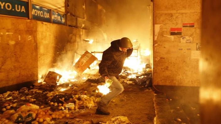 Straßenkampf in der Ukraine: Ein Demonstrant rennt mit einem Brandsatz auf die Sicherheitskräfte zu.