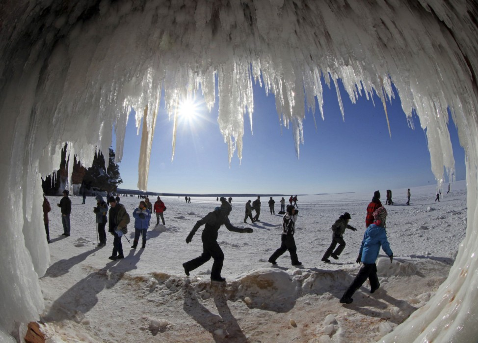 Sightseers look at icicles in sea caves of the Apostle Islands National Lakeshore of Lake Superior