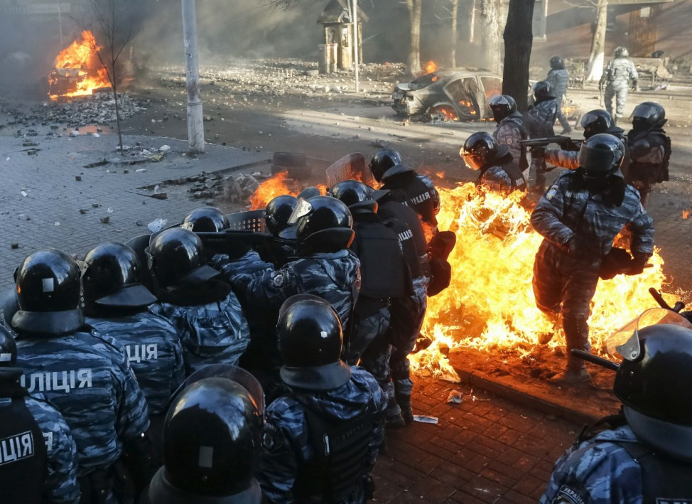 Riot policemen stand guard as they are hit by fire caused by molotov cocktails hurled by anti-government protesters during clashes in Kiev