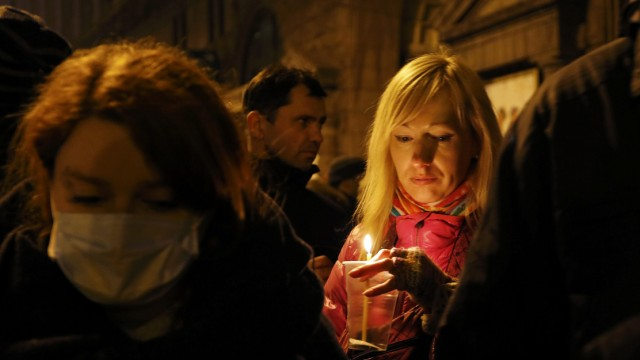 Woman holds a candle as she attends the transfer of over a dozen of corpses from a hotel lobby to a local hospital following clashes with riot police at Independence Square in Kiev