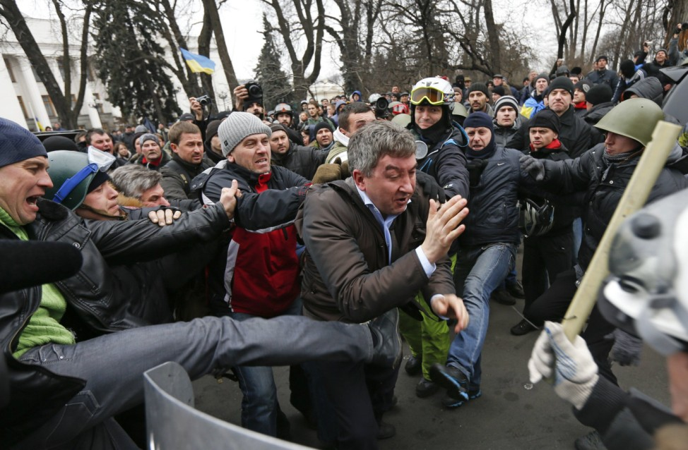 Anti-government protesters attack a deputy of the Party of Regions Vitaly Grushevsky outside the Ukrainian Parliament building in Kiev