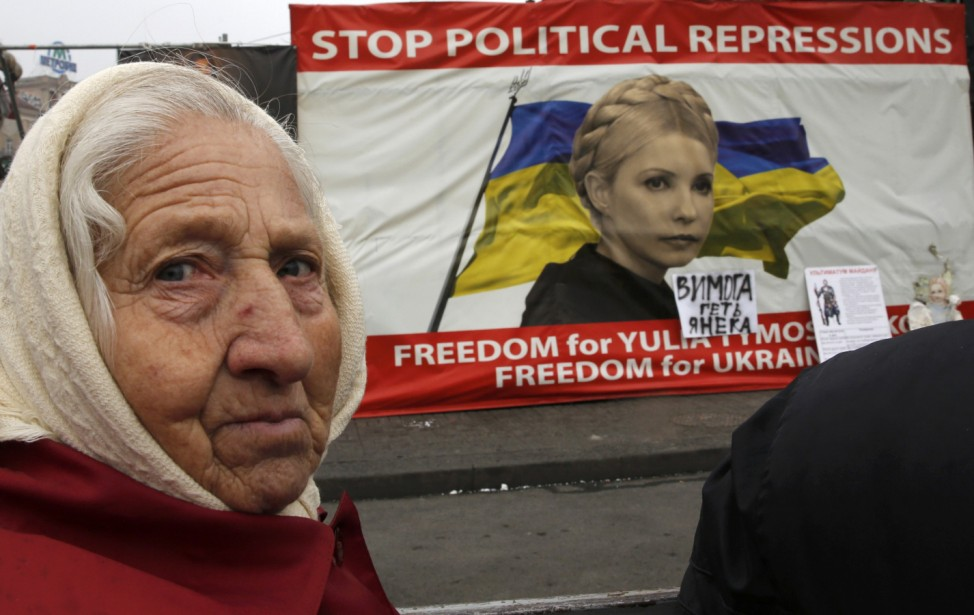 A woman looks on in front of a poster showing jailed Ukrainian opposition leader Tymoshenko in central Kiev