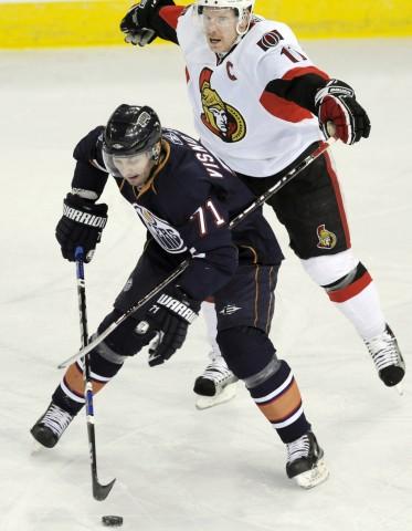 Senators' Alfredsson hooks Oilers' Visnovsky during their NHL hockey game in Edmonton