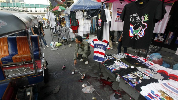 A policeman points at the crime scene following an a bomb blast in Bangkok