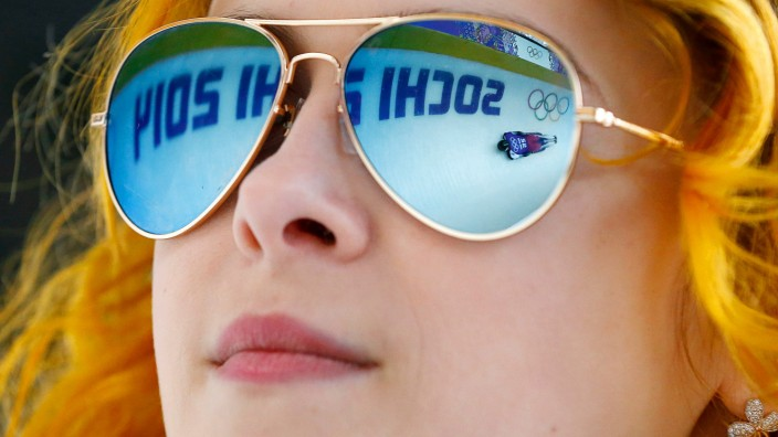 Latvia's Dukurs is reflected in the sunglasses of a volunteer during a men's skeleton training at the Sanki Sliding Center