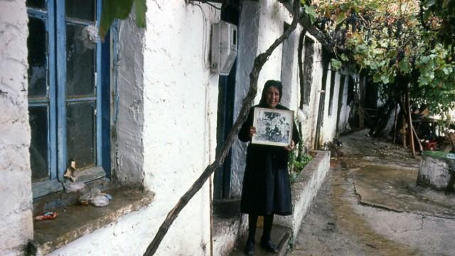 Eleni Rouska, Überlebende des Massakers, mit einem Bild ihres getöteten Mannes Lyngiádes 1993.