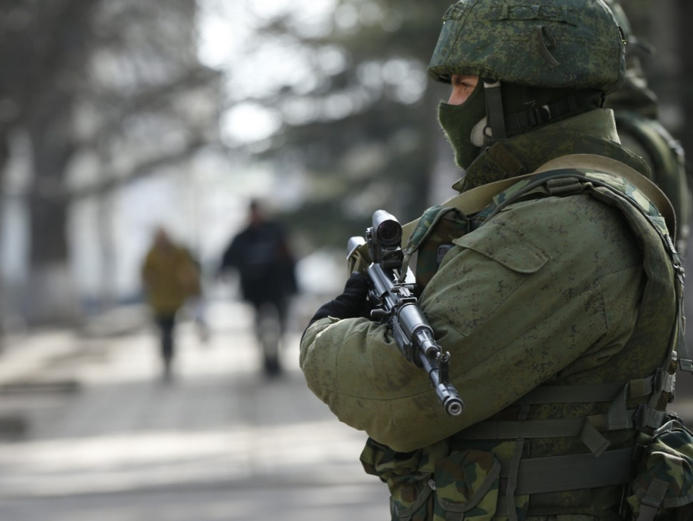 An armed man patrols near the regional parliament building in the Crimean city of Simferopol