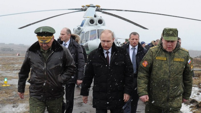 Russia's President Putin, accompanied by Russian Defence Minister Shoigu, walks to watch military exercises upon his arrival at Kirillovsky firing ground in Leningrad region