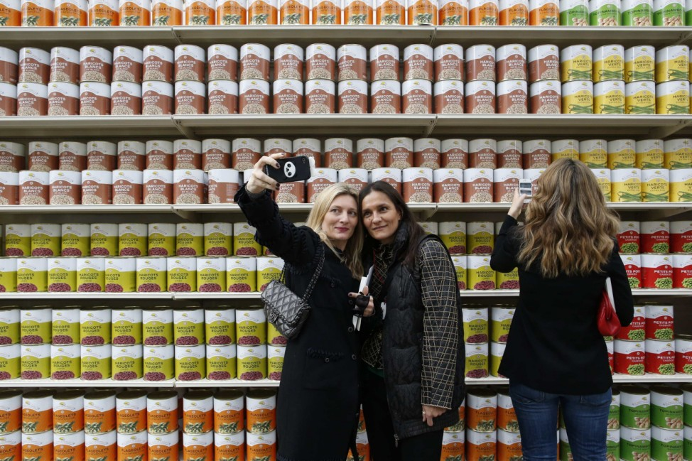 Guests take a selfie in front of supermarket shelves at the Grand Palais transformed into a 'Chanel Shopping Center' during Paris Fashion Week