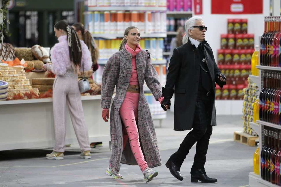 German designer Lagerfeld and model Delevingne appear at the end of his Fall/Winter 2014-2015 women's ready-to-wear collection show for French fashion house Chanel at the Grand Palais transformed into a 'Chanel Shopping Center' during Paris Fashion Week