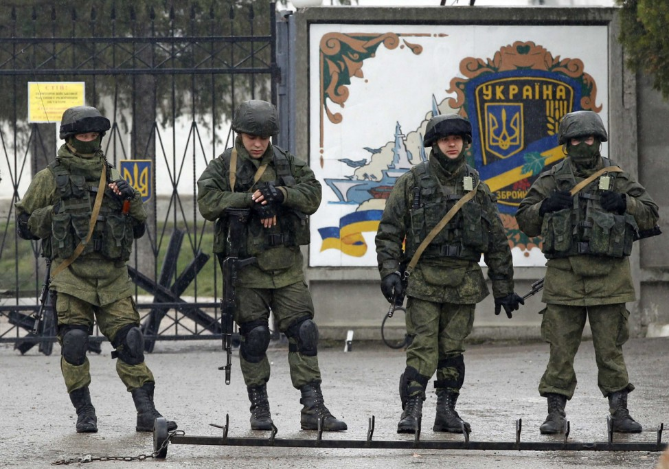 Uniformed men, believed to be Russian servicemen, stand guard outside a Ukrainian military base in the village of Perevalnoye outside Simferopol