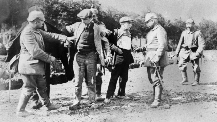 Deutsche Soldaten durchsuchen belgische Zivilisten an der Westfront, 1914