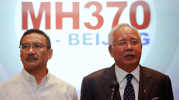 Malaysian PM Razak addresses reporters as Transport Minister Hussein stands by him, at Kuala Lumpur International Airport