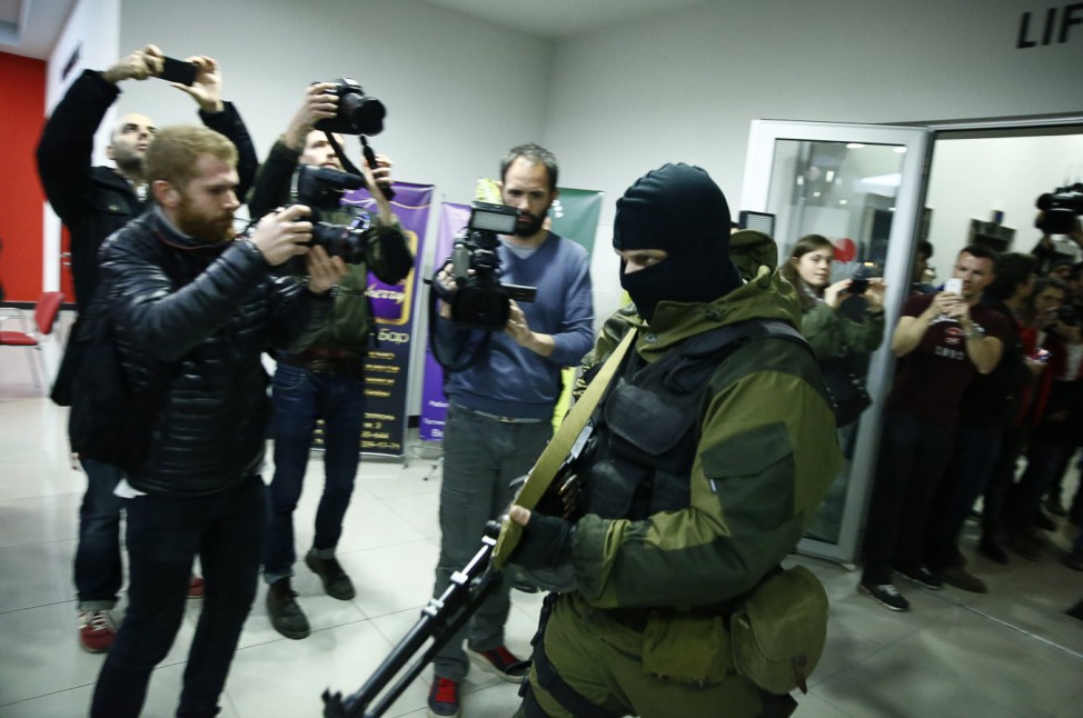 An armed man leaves the Moscow hotel in Simferopol