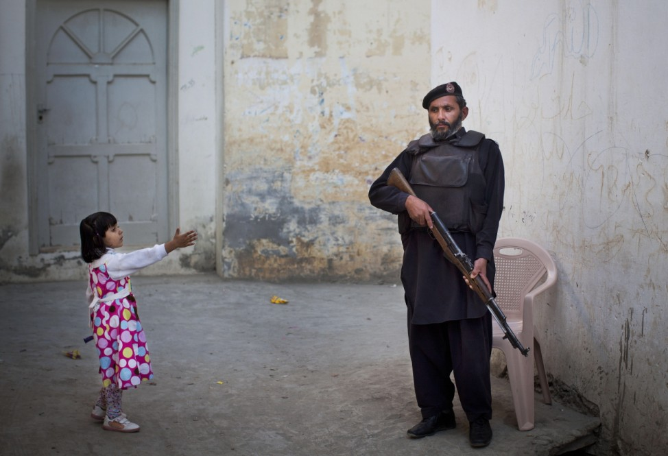 In this Nov. 15, 2012 photo, a young girl reaches out to greet a Pakistani...