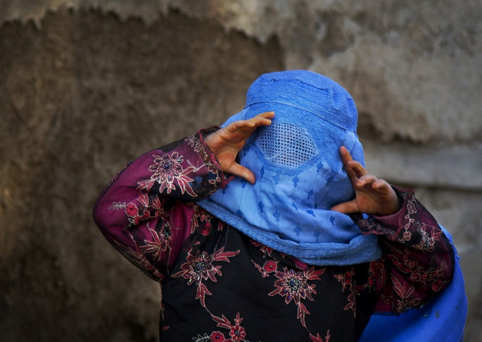 An Afghan girl tries to peer through the holes of her burqa as she plays...