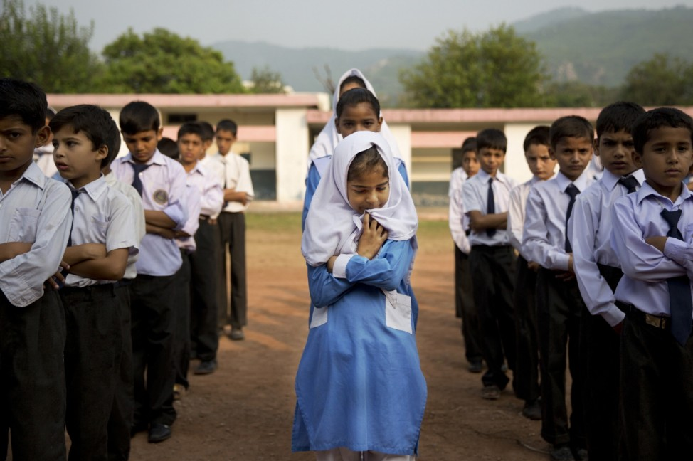 A Pakistani girl lines up among boys for their morning assembly where they...