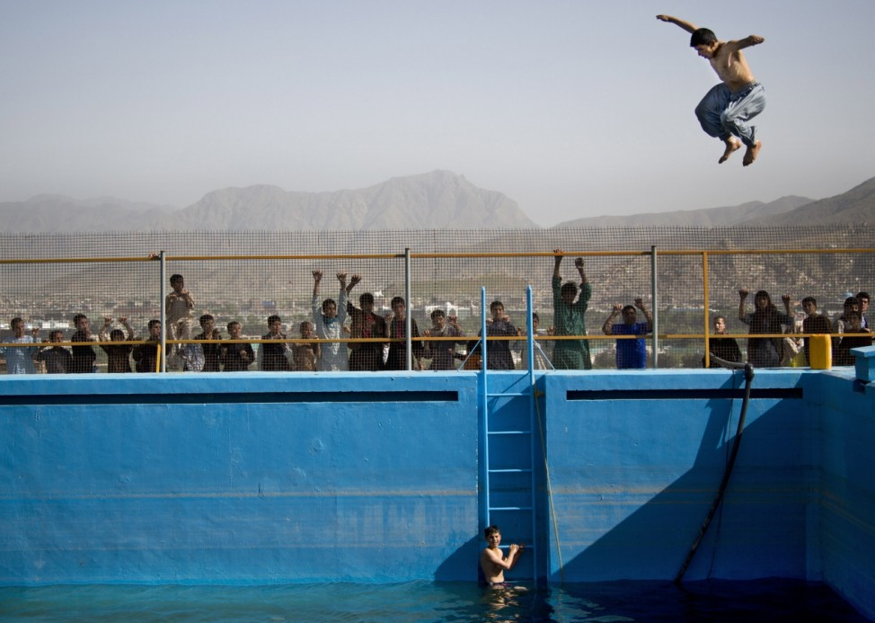 An Afghan man jumps from a diving board into a swimming pool on a hill...