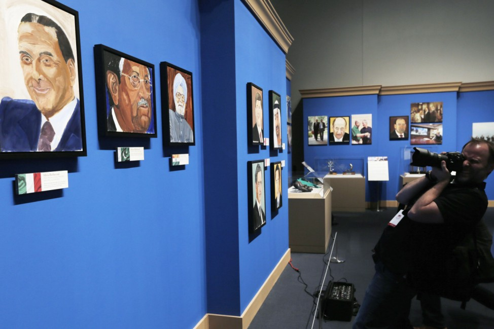 Member of the media photographs portraits of world leaders painted by former U.S. President Bush, on display during 'The Art of Leadership: A President's Personal Diplomacy' exhibit at the George W. Bush Presidential Library and Museum