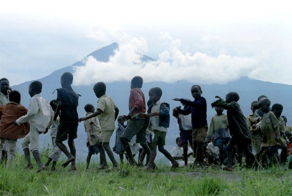 File photo of Rwandan children dancing in a circle in the shadow of one of several volcanoes in Rwanda