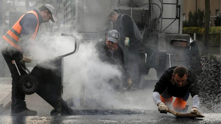 Strassenarbeiter flicken Berliner Strasse