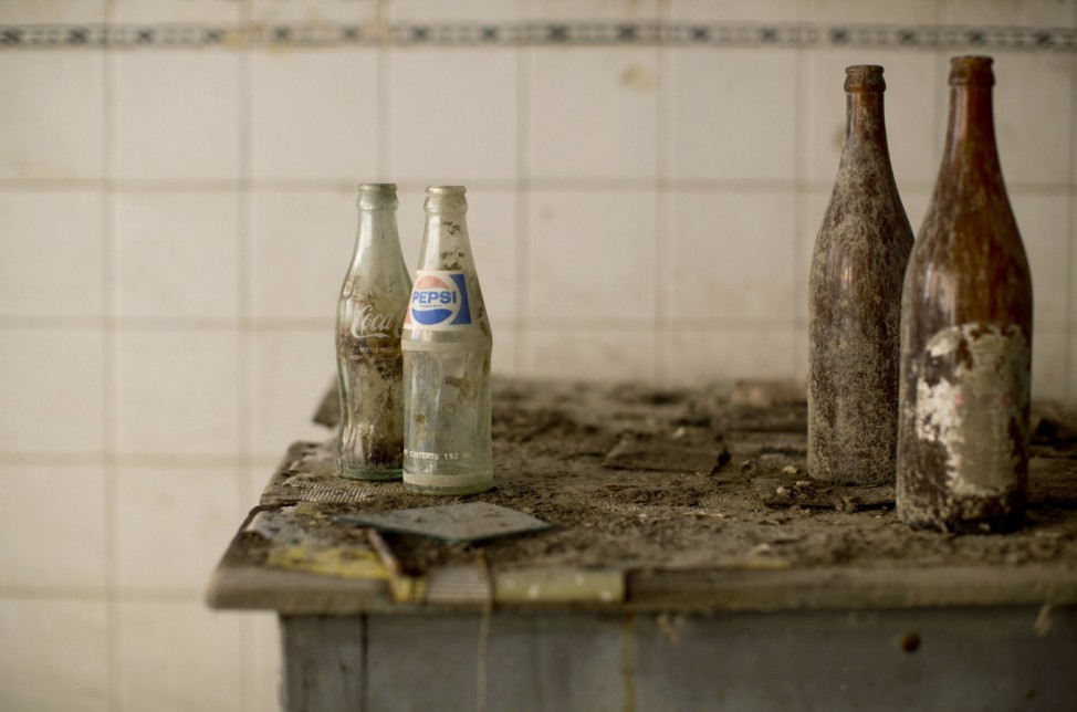 Coca-Cola and Pepsi bottles stand on a table at an abandoned cafe in the United Nations buffer zone in central Nicosia