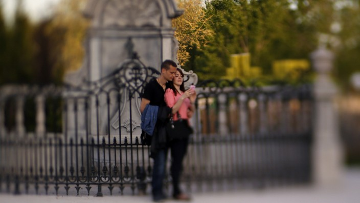 A couple looks at their phone after having taken a photo of themselves by a replica of Brussels' Manneken-Pis at Parque Europa in Torrejon de Ardoz, in the outskirts of Madrid