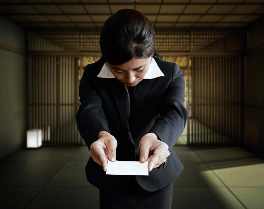 Eine Japanerin nimmt eine Visitenkarte entgegen
