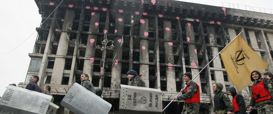 Members of a Maidan self-defence unit walk past a burnt building on Independence Square in Kiev