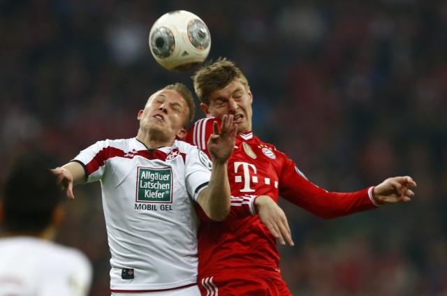 Bayern Munich's Kroos and 1.FC Kaiserslautern's Ring jump for header during German soccer cup semi-final match in Munich
