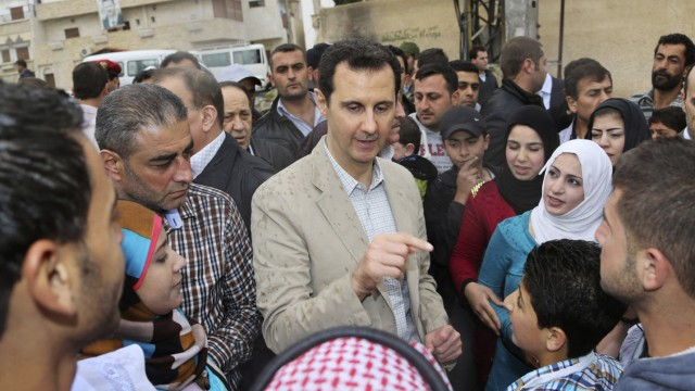 Syrian President Bashar al-Assad (C) chats with people during his visit to Ein al-Tinah village