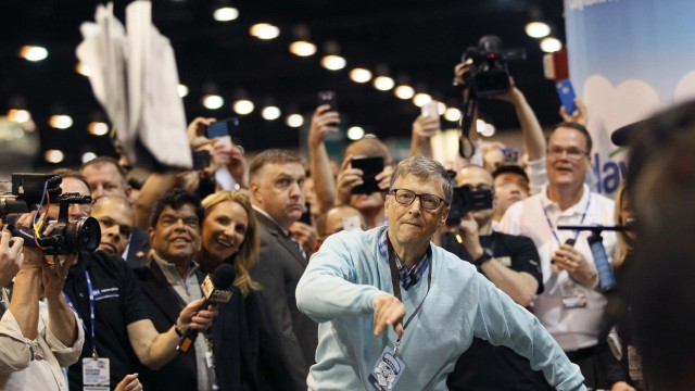 Microsoft founder and technology advisor Gates throws a newspaper during a competition at a trade show at the Berkshire Hathaway annual meeting in Omaha