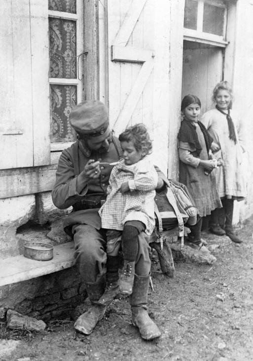 Deutscher Soldten mit kleinem Jungen, 1914 | German soldier feeds a French boy, 1914