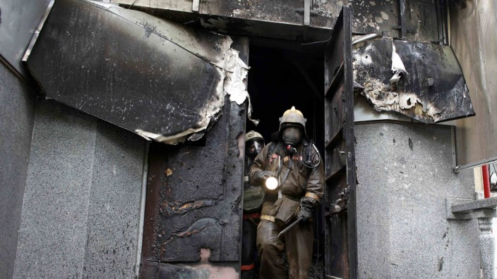 Firefighters inspect the burnt police headquarters after an Ukrainian forces attempt to drive out pro-Russian militants, and the building caught fire in Mariupol