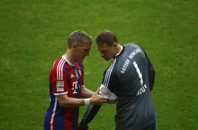 Bayern Munich's Schweinsteiger attaches captains armband to goalkeeper Neuer as he leaves pitch injured in German first division Bundesliga soccer match against VfB Stuttgart in Munich