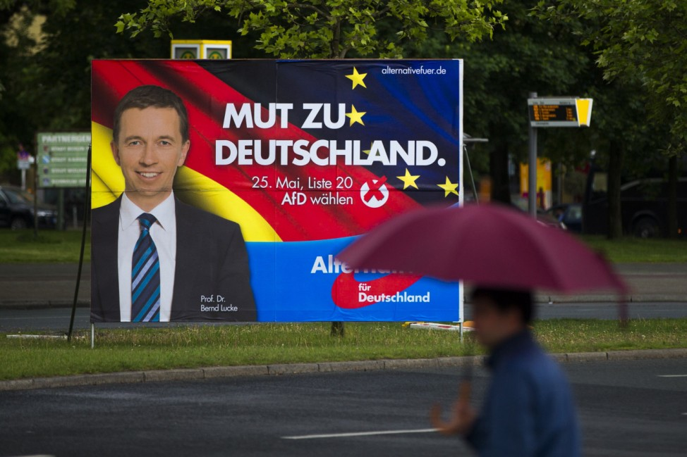 A man walks past an election poster of Lucke, chairman of German anti-euro party the AfD, for the European elections in Berlin