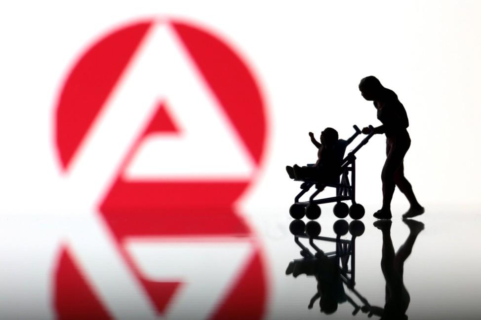 Miniatur Figur einer alleinerziehenden Frau mit Kind im Kinderwagen geht vor dem Logo der Bundesagen