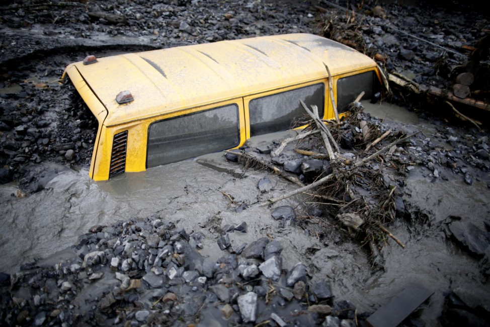 A vehicle stranded in mud is seen on a street that was hit by floods in Topcic Polje