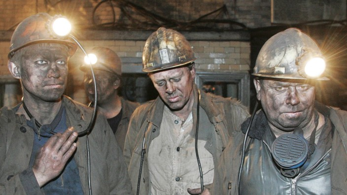 Ukrainian miners stands outside a pit in the town of Donetsk
