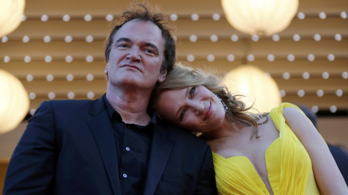 Director Quentin Tarantino and actress Uma Thurman pose on the red carpet they arrive for the screening of the film 'Sils Maria' in competition at the 67th Cannes Film Festival in Cannes