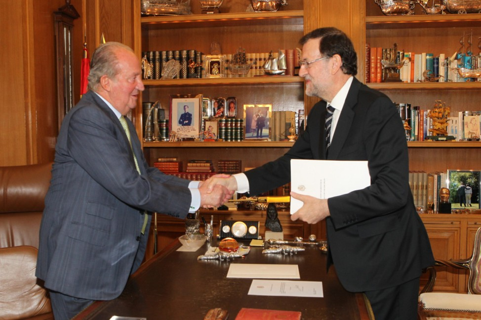 Spain's King Juan Carlos shakes hands after giving his abdication notice to PM Rajoy at the Zarzuela Palace