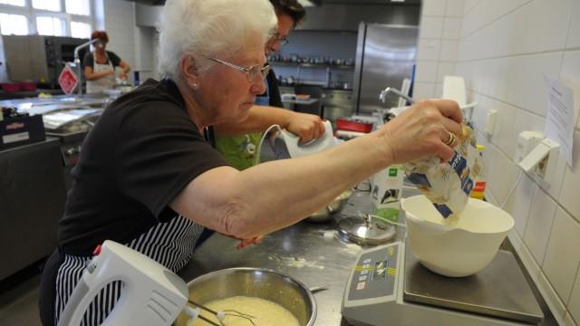 Geschäftsidee mit sozialer Komponente: In der Kuchenbäckerei: eine Seniorin bei der Zubereitung einer süßen Leckerei.