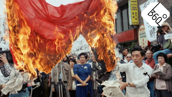 The flag of China is burned during a memorial service in Los Angeles on...