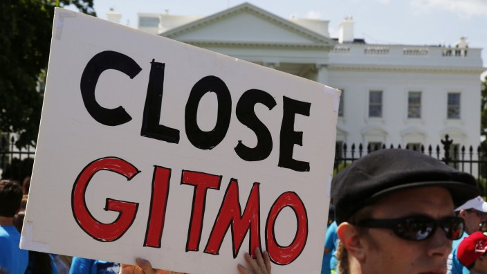 Activist holds a sign at a rally next to the White House in Washington calling for the closure of the U.S. run Guantanamo Bay prison in Cuba
