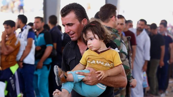 Gewalt im Irak: Flucht aus Mossul: Zivilisten in der überwiegend von Kurden bewohnten Stadt versuchen sich vor den anrückenden Isis-Kämpfern in Sicherheit zu bringen.