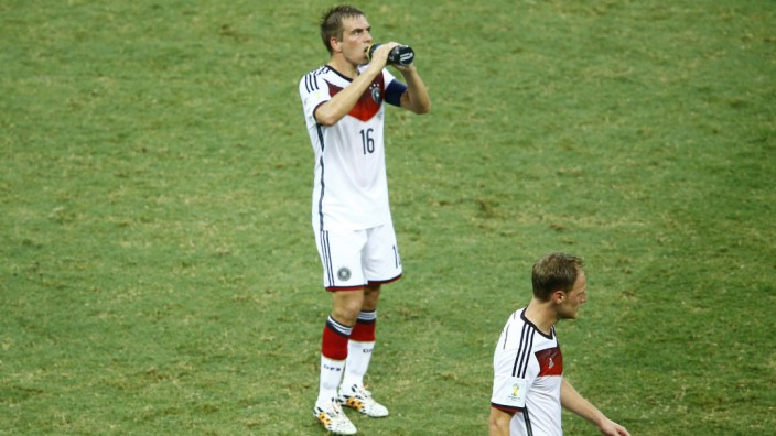 Germany's Lahm drinks water near team coach Loew and teammate Mertesacker during their 2014 World Cup Group G soccer match against Ghana  at the Castelao arena in Fortaleza