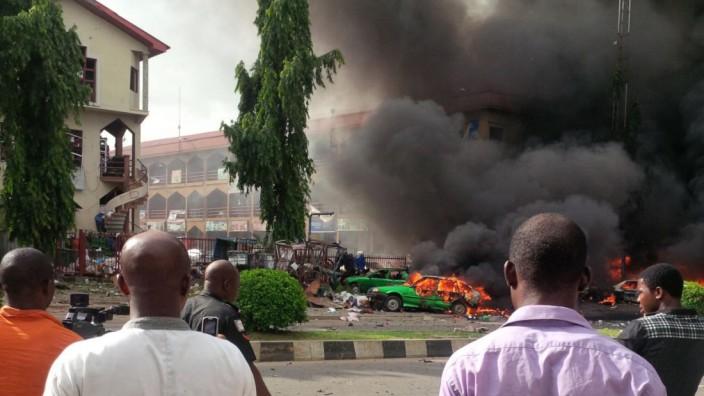 Anschlag in Nigerias Hauptstadt: Nach der Explosion in einem Einkaufszentrum in Abuja: Parkende Autos gehen in Flammen auf, schwarzer Rauch dringt aus dem Gebäude.