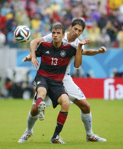 Gonzalez of the U.S. fights for the ball with Germany's Mueller during their 2014 World Cup Group G soccer match at the Pernambuco arena in Recife