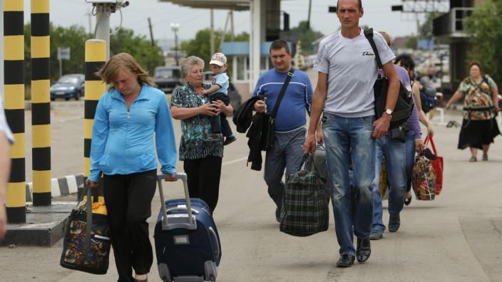 UNHCR zu Ukraine: Auf dem Weg nach Russland: Menschen tragen am 26. Juni ihre Habseligkeiten über die ukrainisch-russische Grenze in Izvaryne in der Lugansk-Region.